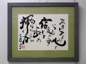 額縁に入った岡田さんが書いた書道の写真