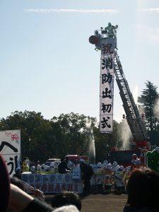 垂れ幕「祝消防出初式」と放水の写真